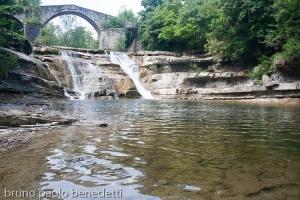 cascate della brusia con ponte di sassi a schiena d'asino a portico di romagna sul fiume montone
