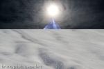 piramide di cristallo blu su cielo nero e campo che assomiglia ad un deserto e sole su in cielo cuspide piramide
