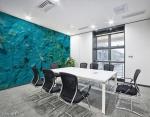 murale astratto con trama di colore grezza che riproduce un effetto di pittura naturale con rilievi, linee spezzate e sfumature gialle applicata sulla parte di una sala riunioni